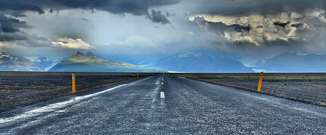 Symbolbild: Foto einer geraden Strasse, die bis zum Horizont reicht unter Gewitterwolken