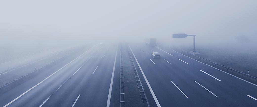 Symbolbild zum Artikel Insolvenzantragspflicht: Foto einer Autobahn im Nebel mit Schild Ausfahrt