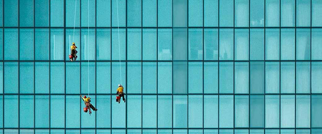 Foto einer Glasfassade mit 3 Gebäudereinigern