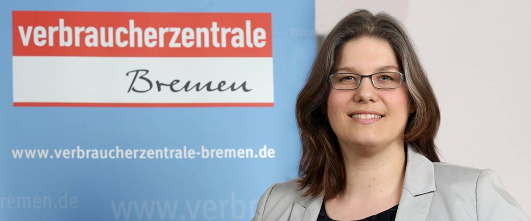 Porträt Dr Annabel Oelmann vor einer Tafel mit dem Logo der der Verbraucherzentrale Bremen